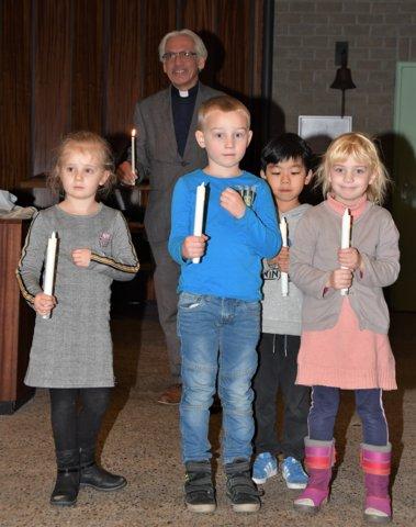 Vier kinderen staken de adventskaarsen aan